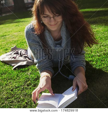 Beautiful woman reading book in nature. Young attractive student in red dress studying and reading a book. (Relax rest education concept recreation).