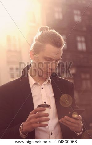 young hipster businessman holding phone and a coffee (outdoors)
