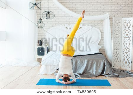 Woman makes a stand on her head near the bed in the bedroom.