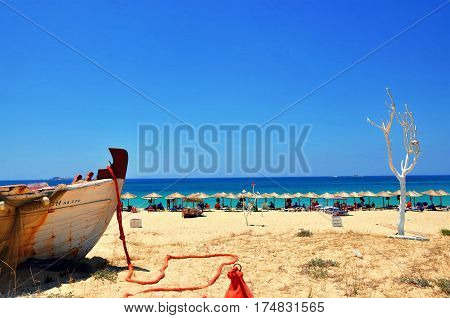 Beach umbrellas white whitewashed tree and part of boat beautiful scenery in sunny summer day on Naxos island Greece