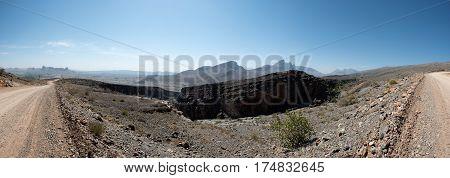 An arid mountainous landscape under a cloudless blue sky