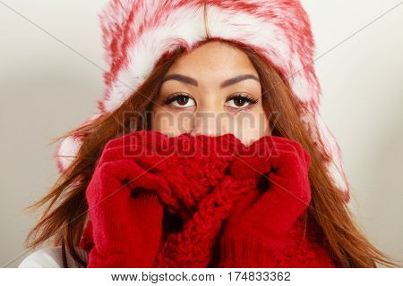 Winter clothing fashion concept. Closeup of young mulatto woman covering her face with hands wearing red gloves and scarf. Mixed race girl in wintertime clothes fur cap studio shot