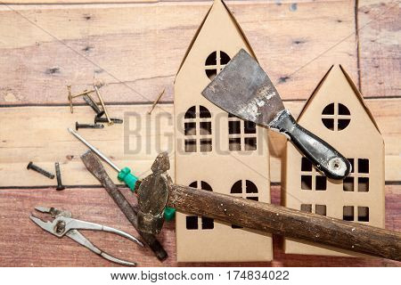 Hammer, putty knife, screwdriver and tools for repair and construction of houses and cardboard on the wooden background. Concept of repair and construction