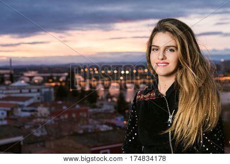 spring outdoor porttrait of young pretty blonde girl with city background.