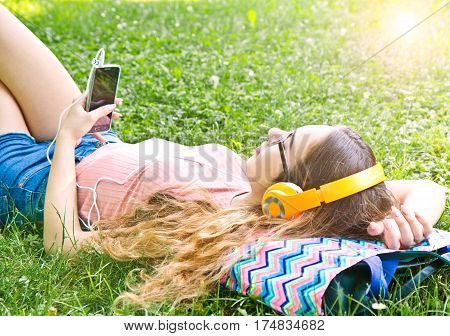 Beautiful girl relaxing and listen music in the headphones in the park