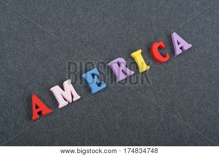 America word on black board background composed from colorful abc alphabet block wooden letters copy space for ad text. Learning english concept.