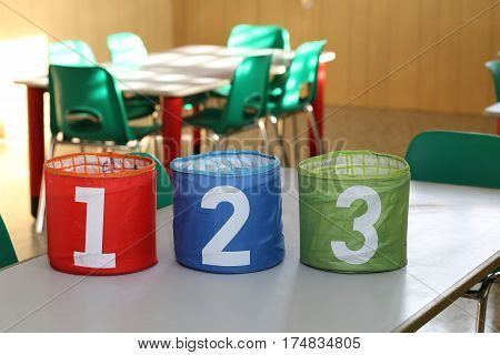 three big jars with big numbers one two three in a classroom of a school