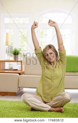 Attraktive Frau sitzen auf dem Boden des Wohnzimmers stretching mit kleinen Lächeln.?