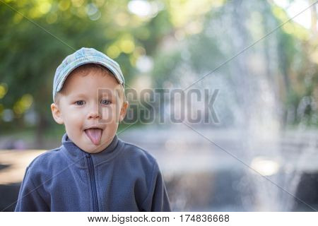Boy Showing Tongue, Playing Outdoors