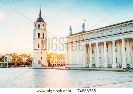Vilnius, Lithuania. The View Of Cathedral Square With Bell Tower And Cathedral Basilica Of St. Stanislaus And St. Vladislav In Summer Sunset With Sunbeam Under Blue And Yellow Sky.