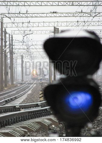 Railway traffic light shows blue signal on railway with blur effect and railway with train as the background