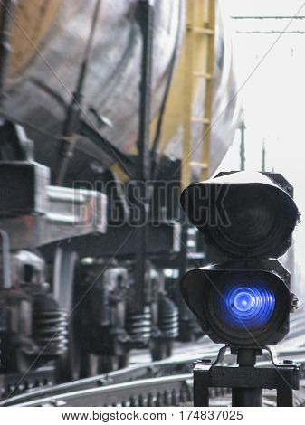 Railway traffic light shows blue signal on railway with blur effect and railway with freight train as the background .
