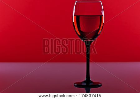 Glass of red french wine on a red background
