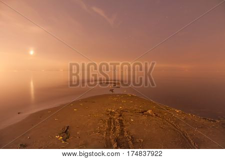 Cape on sandy beach of Gulf of Finland. Night scene with shining moon. Seashore in moonlight. Saint-Petersburg.