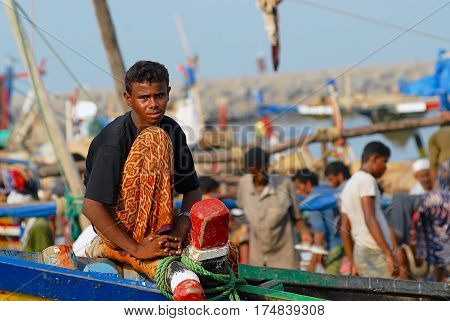 AL HUDAYDAH, YEMEN - SEPTEMBER 17, 2006: Unidentified fisherman sits at the front side of the fishing boat just arrived to the port in Al Hudaydah, Yemen.