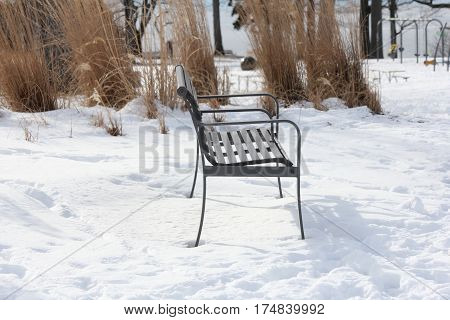 Vacant park bench in a snow filled park during the winter season.