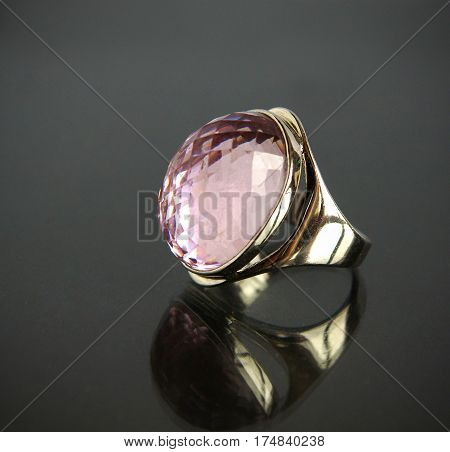 White gold or silver Jewel ring with colored gemstone closeup on black background with selective focus