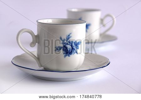 Antique porcelain tea cup and saucer with local focus on the background of blurred second cup