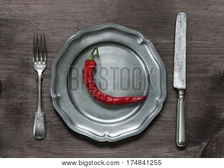 Red hot chilli pepper on vintage pewter plate as well as fork and knife on old brown dark wooden board