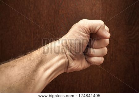 Male Fist Over Dark Brown Wooden Wall