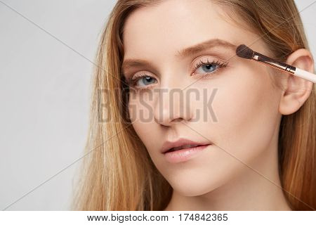 Woman beauty portrait make-up visage gray white background with brushes isolated hair cosmetic closeup