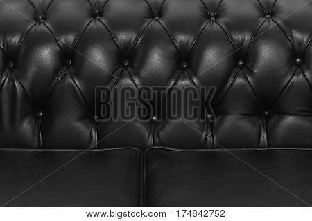 Black leather upholstery on retro sofa detail