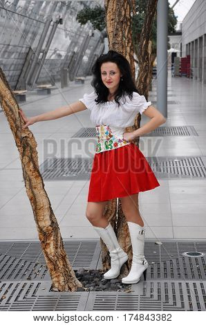 pretty woman or sexy cute girl with adorable smiling face in national ukrainian embroidered belt red skirt and white blouse boots near tree has long brunette hair