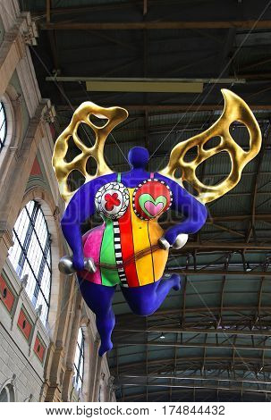 ZURICH HB SWITZERLAND - MARCH 16 2015: View of a statue of a guardian angel by Niki de Saint Phalle situated inside of the main train station in Zurich