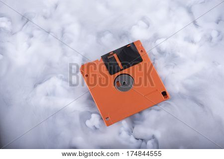 Orange floppy disk in the clouds. Conceptual image
