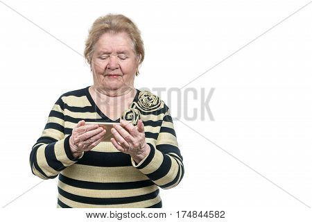 Old woman holds a smartphone with two hands and looking at it, isolated on a white background