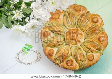 Creative homemade cake of yeast dough with stuffed of cottage cheese. The original cake in shape of flower and card for your text. Festive dessert for Mother's Day birthday anniversary. Top view