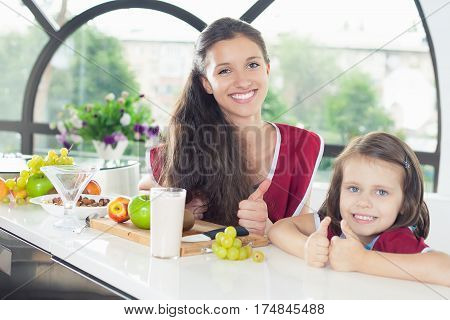 Cute little girl cooking with her sister. Healthy food, cooking healthy salad with fruits ingredients. Mom and daughter cooking together. Shows thumbs up.