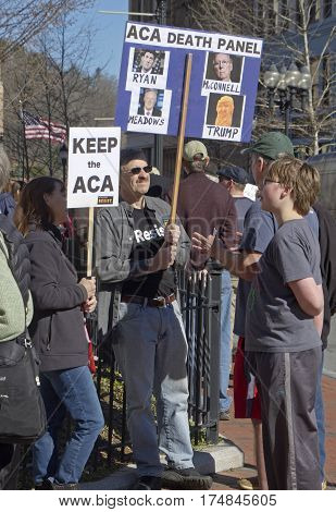 Asheville North Carolina USA - February 25 2017: Demonstrators at an Affordable Care Act (ACA) rally hold signs saying