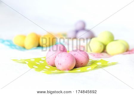 Spring colorful easter eggs separated by color in small colorful fabrics with soft blur on the background all in top of a white sheet.