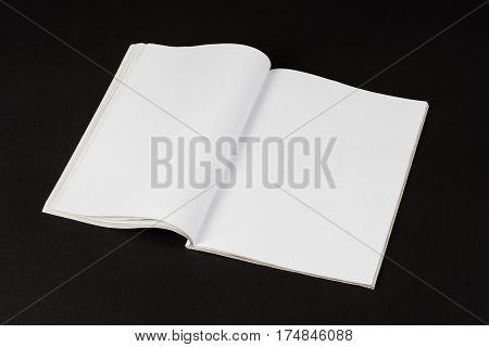 Mock-up magazine or catalog on black table. Blank page or notepad on paper background. Blank page or notepad for mockups or simulations.