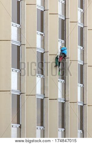 Alpinist window cleaning office building facade hanging cable ..