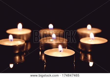 Group of tea candles on a black background. Selective focus.