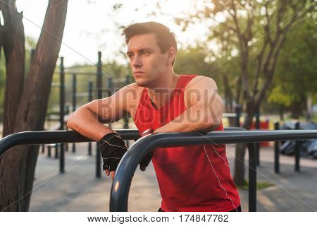 Young athletic man taking a break during a working out outdoor