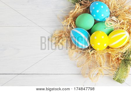 Easter Eggs In The Nest On Rustic White Background