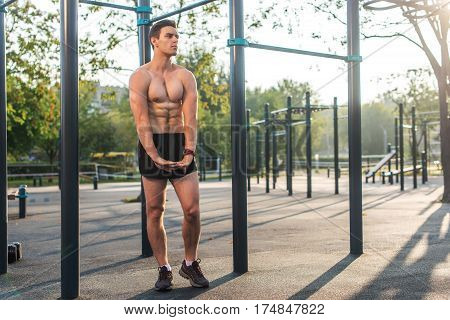Fitnes man posing on street fitness station showing his muscular body Full lenght portrait