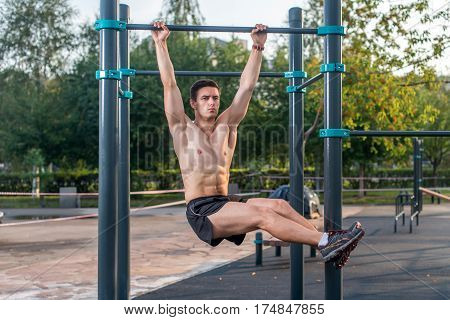 Athlete hanging on fitness station performing legs raises. Core cross training working out abs muscles.