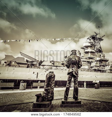A lone Sailor Statue looking over a World War Two era battleship.
