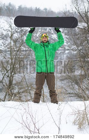 Snowboarder In Bright Clothes Posing With A Snowboard