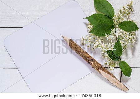 Flowering bird cherry branch with a card for the text on a white wooden background. Can be used as floral backgrounds holiday greetings and invitations cards