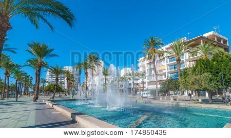 Bright morning sunshine on town square pedestrian park & fountain.  Hotels in background line the square. Fountain park in Sant Antoni De Portmany, Ibiza.