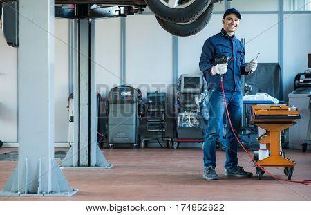 Smiling mechanic at work. Full length portrait