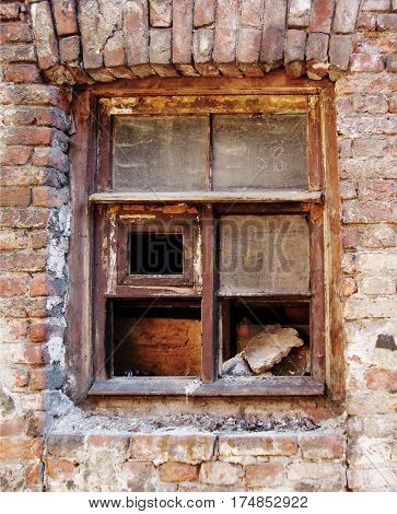 The window frame of a ruined house. Destroyed building as a symbol of devastation, desolation, destruction, loss, or war.
