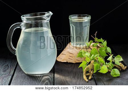 Spring useful vitamin drink. Fresh cold birch juice in a jug and glass and birch branches on a dark background. Concept of healthy and vitamin food