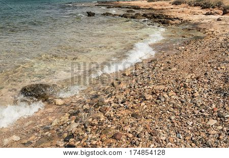 view of the blue sea shore with small pebbles