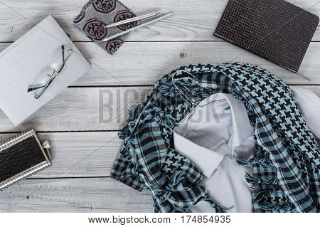 Fragment of a men's shirt with a keffiyeh on a hanger diary water bottle on a wooden painted surface. The pastel colors